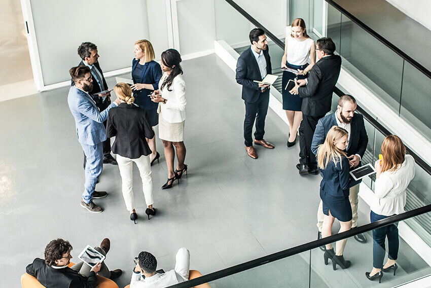 Overhead view of a group of standing people talking. Aston Carter Recruitment Articles.