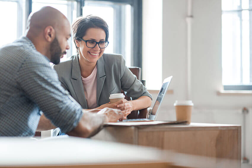 Woman and man working together in front of a laptop.  Aston Carter Recruitment Articles.