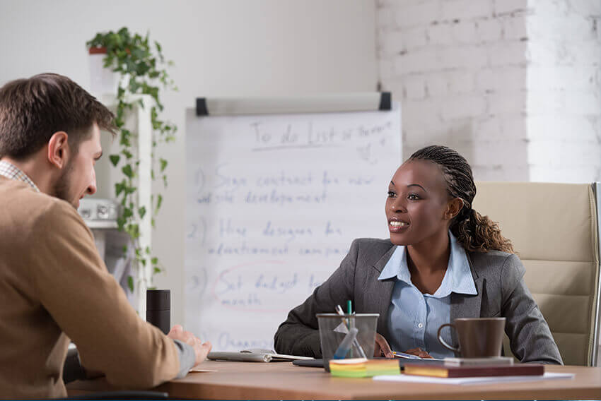 Woman and man interviewing, while sitting at a desk.  Aston Carter Recruitment Articles.