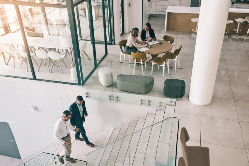Overhead view of inside an office building with two men walking up stairs | Astoncarter.com